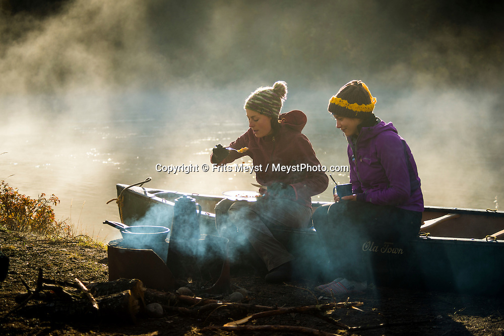 Yukon Territory, Canada, September 2014. breakfast next to the campfire in the early morning sun during autumn fog on the steaming Yukon river. During this Yukon River canoe trip we paddled part of the Klondike Gold Rush route of 1898. We camped on the banks of the Yukon River in authentic northern wilderness and explored the gold rush relics on the way. Photo by Frits Meyst / MeystPhoto.com