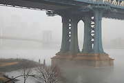 Brooklyn Bridge with Manhattan Bridge pillar in the foreground during a morning fog