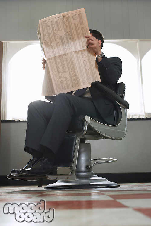 Business man reading newspaper waiting in barber shop