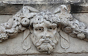 Mask and garland frieze from the Portico of Tiberius on the Southern portico of the Agora, 1st century AD, Aphrodisias, Aydin, Turkey. The Sculpture School at Aphrodisias was an important producer of carved marble sarcophagi and friezes from the 1st century BC until the 6th century AD. The Portico of Tiberius was built under the reign of Tiberius and has many examples of mask and garland friezes, consisting of the heads of gods, goddesses, theatrical characters, mythological figures or masks, each with a distinct facial expression, between hanging garlands of leaves, fruit and flowers. This example shows the gaunt face of a sad old man with a beard. Aphrodisias was a small ancient Greek city in Caria near the modern-day town of Geyre. It was named after Aphrodite, the Greek goddess of love, who had here her unique cult image, the Aphrodite of Aphrodisias. The city suffered major earthquakes in the 4th and 7th centuries which destroyed most of the ancient structures. Picture by Manuel Cohen