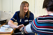 The prison nurse takes the blood pressure of an inmate in the prison medical unit. HMP/YOI Askham Grange is a women's open prison serving the Yorkshire area with a capacity of 128 women. It has extensive education, training and mother and Baby facilities.