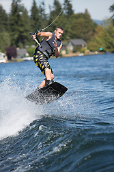 United States, Washington, Lake Sawyer, teen boy wakeboarding.  MR