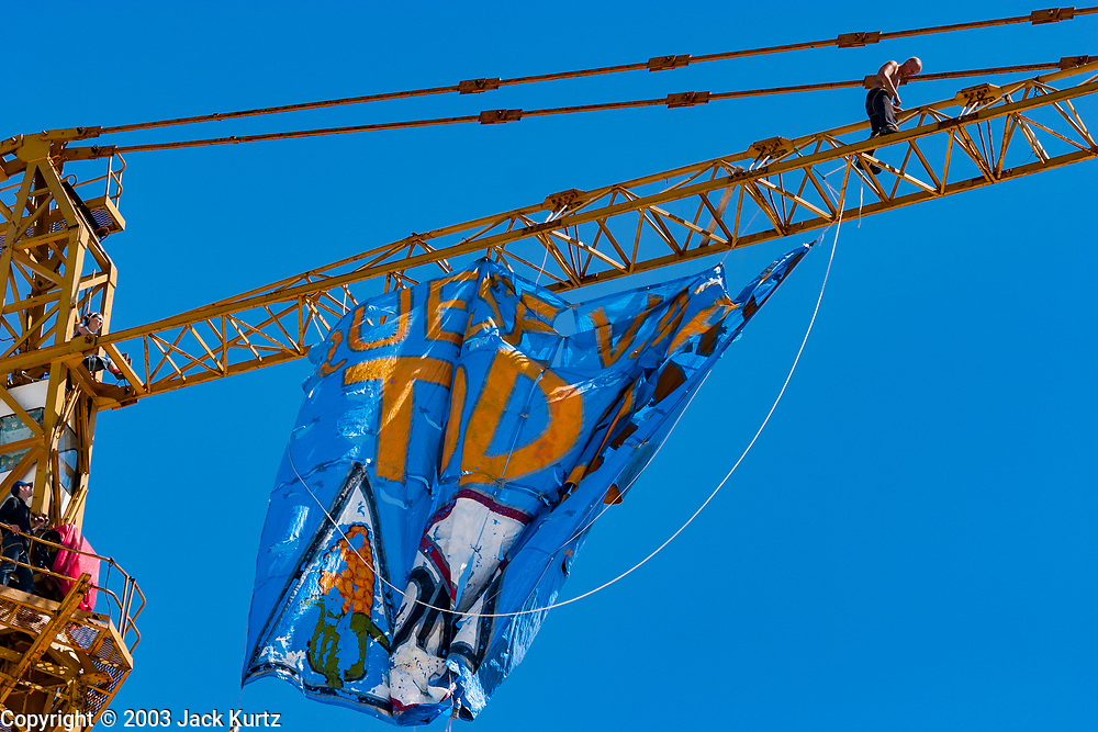 12 SEPTEMBER 2003 - CANCUN, QUINTANA ROO, MEXICO:  Members of Greenpeace hang a protest banner from a construction crane during the WTO protests in Cancun. Tens of thousands of protesters, mostly farmers, came to Cancun for the fifth ministerial of the World Trade Organization (WTO). They were protesting against developed nations pushing to get access to agricultural markets in developing nations. The talks ultimately collapsed after no progress with no agreements reached between the participants.          PHOTO BY JACK KURTZ