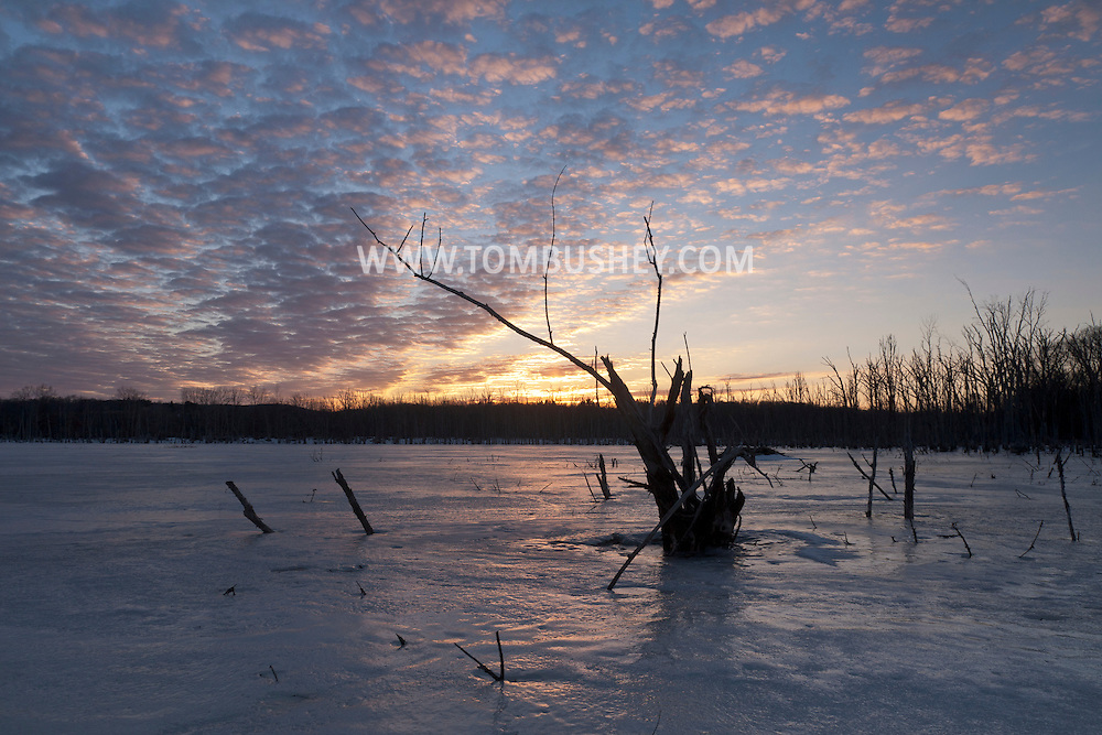 Middletown, New York - Sunset clouds over a frozen lake on  March 17, 2014.