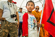 01 MAY 2013 - BANGKOK, THAILAND:  A boy wearing a Yingluck Shinawatra (Prime Minister of Thailand) tee shirt, attends a Red Shirt rally at the Constitutional Court in Bangkok. Several hundred Thai Red Shirts, members of the United Front for Democracy against Dictatorship (UDD), have been camped out at Thailand's Constitutional Court, which oversees matters related to the Thai constitution and constitutional amendment. The Red Shirts are protesting the court's decision to consider a petition regarding the constitutionality of the constitutional amendments that have been proposed by the government. The group is arguing that by considering the petition, the Court is impeding the powers of the legislative branch.  PHOTO BY JACK KURTZ