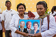"30 JANUARY 2013 - PHNOM PENH, CAMBODIA:    Women mourning Cambodian King Norodom Sihanouk hold up a portrait of the King (center) with his wife and son. Sihanouk (31 October 1922 - 15 October 2012) was the King of Cambodia from 1941 to 1955 and again from 1993 to 2004. He was the effective ruler of Cambodia from 1953 to 1970. After his second abdication in 2004, he was given the honorific of ""The King-Father of Cambodia."" Sihanouk held so many positions since 1941 that the Guinness Book of World Records identifies him as the politician who has served the world's greatest variety of political offices. These included two terms as king, two as sovereign prince, one as president, two as prime minister, as well as numerous positions as leader of various governments-in-exile. He served as puppet head of state for the Khmer Rouge government in 1975-1976. Most of these positions were only honorific, including the last position as constitutional king of Cambodia. Sihanouk's actual period of effective rule over Cambodia was from 9 November 1953, when Cambodia gained its independence from France, until 18 March 1970, when General Lon Nol and the National Assembly deposed him. Upon his final abdication, the Cambodian throne council appointed Norodom Sihamoni, one of Sihanouk's sons, as the new king. Sihanouk died in Beijing, China, where he was receiving medical care, on Oct. 15, 2012. His cremation is scheduled to take place on Feb. 4, 2013. Over a million people are expected to attend the service.        PHOTO BY JACK KURTZ"