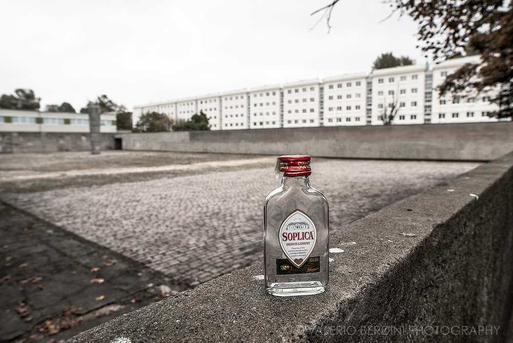 A bottle of Soplica vodka left empty in front of what was the courtyard of Pawiak prison, the place were Nazi tortured Jewish prisoners. Soplica is one of the older brands of Polish vodka, having been first produced in 1891. During the occupation of Poland in World War II, Kasprowicz (the brand founder) was deported to Warsaw by the Germans and died there in 1943.