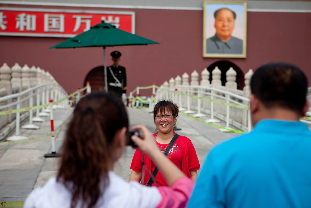 "A woman is getting photographed at the main gate of ""The Forbidden City"" which was the Chinese imperial palace from the Ming Dynasty to the end of the Qing Dynasty. It is located in the middle of Beijing, China. Beijing is the capital of the People's Republic of China and one of the most populous cities in the world with a population of 19,612,368 as of 2010."