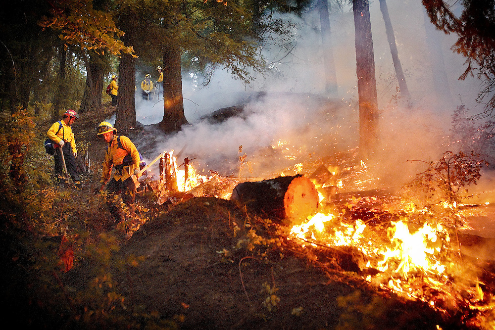 JEROME A. POLLOS/Press..Coeur d'Alene firefighters dig a fire line on the west side of a fire on Tubbs Hill last August. UI is offering the nation's first and only bachelor's degree program focusing on wildland fire ecology and management.