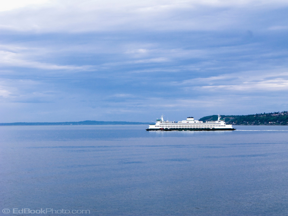 Washington State Ferry Crosses Puget Sound to Bremerton on the Kitsap Peninsula on a cloudy day with the Olympic Mountains in the distance.