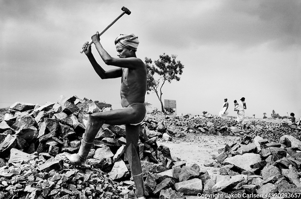 A bonded labourer in a stone quarry in India. They never see the books and don't know how much they owe the landlord.