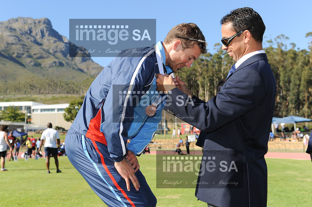 STELLENBOSCH, South Africa - Saturday 13 April 2013, Marc Mundell receives his medal from Mr Malcolm Salida during day 2 of the South African Senior Athletics championships at the University of Stellenbosch's Coetzenburg stadium.Photo by Roger Sedres/ ImageSA