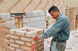 Young man learning brick laying skills,