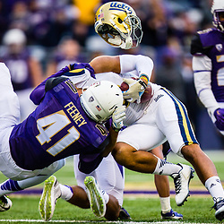 SEATTLE, WASHINGTON - NOVEMBER 8: Washington Husky linebacker Travis Feeney (41) knocks the helmet off of a UCLA Bruins player at Husky Stadium in Seattle, WA. (Photo by Christopher Mast/247Sports)