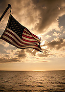 US Flag with sunset over the ocean