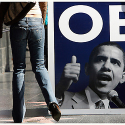 A couple walks past a poster of Democratic presidential candidate, Senator Barack Obama along Hollywood Blvd in front of the Kodak Theatre where Senator Obama and Hillary Rodham Clinton held a presidential candidates debate Thursday, January 31, 2008 in Hollywood ,Calif.