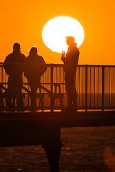 © Licensed to London News Pictures. 21/06/2018 . Aberystwyth Wales UK<br /> UK Weather: The longest day of the year - The Summer Solstice - comes to an end with a dramatic golden sunset over people standing at the end of the seaside pier  in Aberystwyth on the west Wales coast<br /> <br /> photo credit Keith Morris/LNP