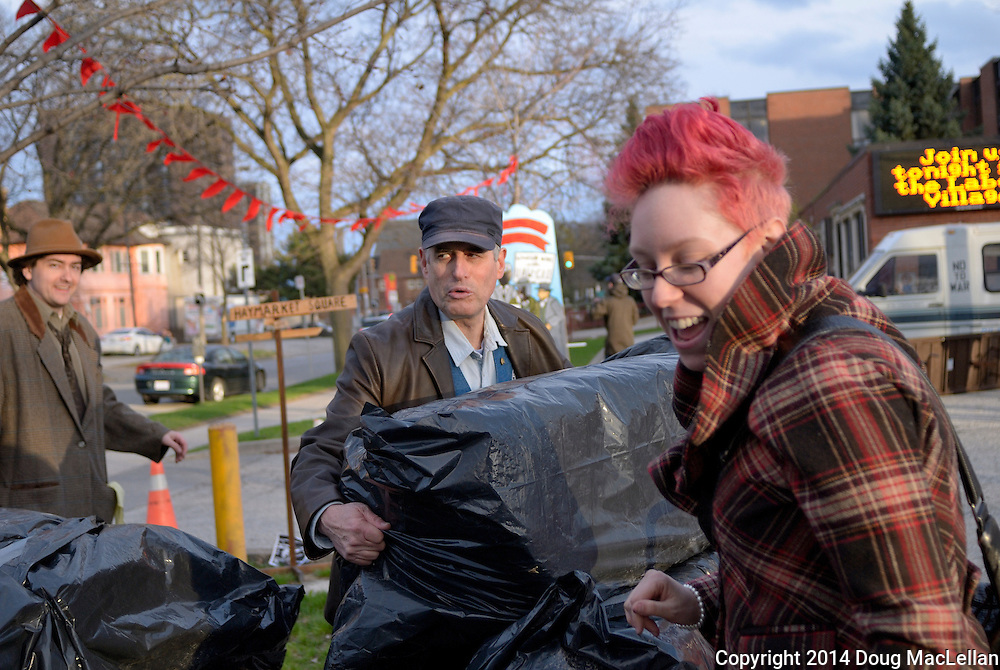 Paul Chislett, centre, and others help move hay at the end of May Day festivities at the frst ever labour Village. May Day is part of May Works Windsor 2014.