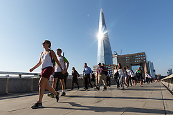 © Licensed to London News Pictures. 24/07/2018. London, UK.  Commuters walk to work over London Bridge whilst the sun reflects off of the London shard during another day of hot and sunny weather in the capital.  Photo credit: Vickie Flores/LNP