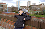 Young boy making a flipping off gesture with housing estates in the background, London, UK, 2000's