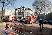 Een politieman op de fiets houdt het publiek op afstand bij een brand op de Mariaplaats in Utrecht.<br /> <br /> A policeman on the bike is keeping the public at a distance at a small fire in a restaurant at the Mariaplaats in Utrecht