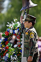 Nick Farina, 14, with the Young Marines of North Idaho, rings a bell as the names of veterans and active duty military service members who died over the past year are read at the Memorial Day service at Memorial Gardens in Coeur d'Alene.