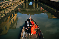 Vietnamese newlyweds have their photo taken in a small boat with the historic Japanese covered bridge reflected behind them in Hoi An, Vietnam.