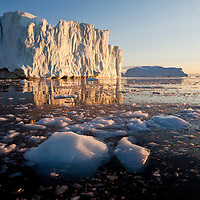 Greenland, Ilulissat, Midnight sun lights massive icebergs calved from Jakobshavn Glacier floating at mouth of Disko Bay on summer evening