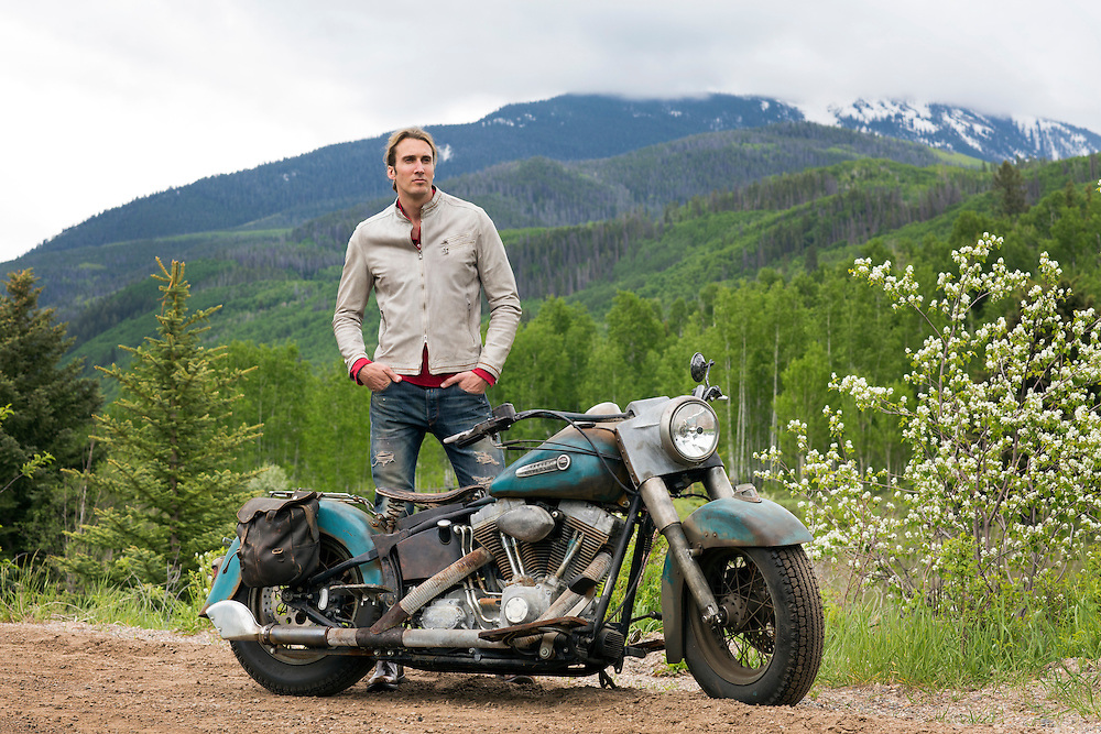 Man in Italian Moto Jacket standing by Harley Davidson on open country road in the Colorado Rockies