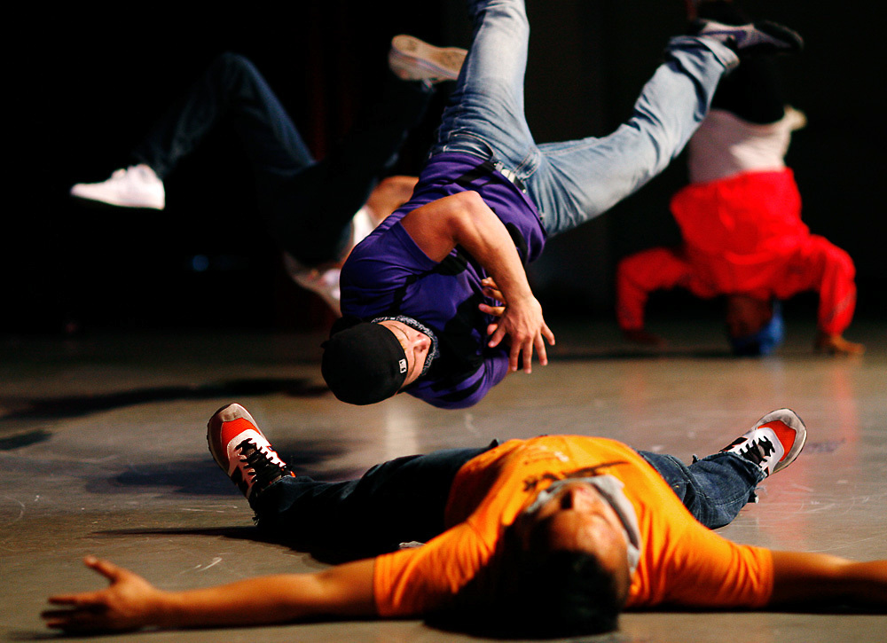 Blayk Johnson, 20, of West Richland, in purple, flips through the air as the TC Rockers finish their set during the 2008 Tri-Cities Talent show. Also pictured are Ryan Lavarias, 21, of Richland, in orange, Daniel King Reds Rojas, 26, of Pasco, in Pink, and Jeff Kim, 22, of Kennewick, in white.