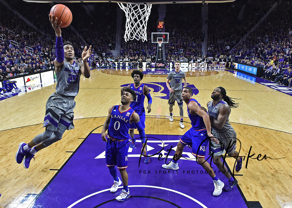 Guard Wesley Iwundu #25 of the Kansas State Wildcats drives to the basket past guard Frank Mason III #0 of the Kansas Jayhawks during the first half at Bramlage Coliseum in Manhattan, Kansas.