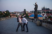 Early morning visitors at Charles Bridge at the St. John of Nepomuk Statue.
