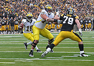 November 05, 2011: Michigan Wolverines quarterback Denard Robinson (16) scrambles while Michigan Wolverines offensive linesman Taylor Lewan (77) blocks Iowa Hawkeyes defensive lineman Dominic Alvis (79) during the first quarter of the NCAA football game between the Michigan Wolverines and the Iowa Hawkeyes at Kinnick Stadium in Iowa City, Iowa on Saturday, November 5, 2011. Iowa defeated Michigan 24-16.