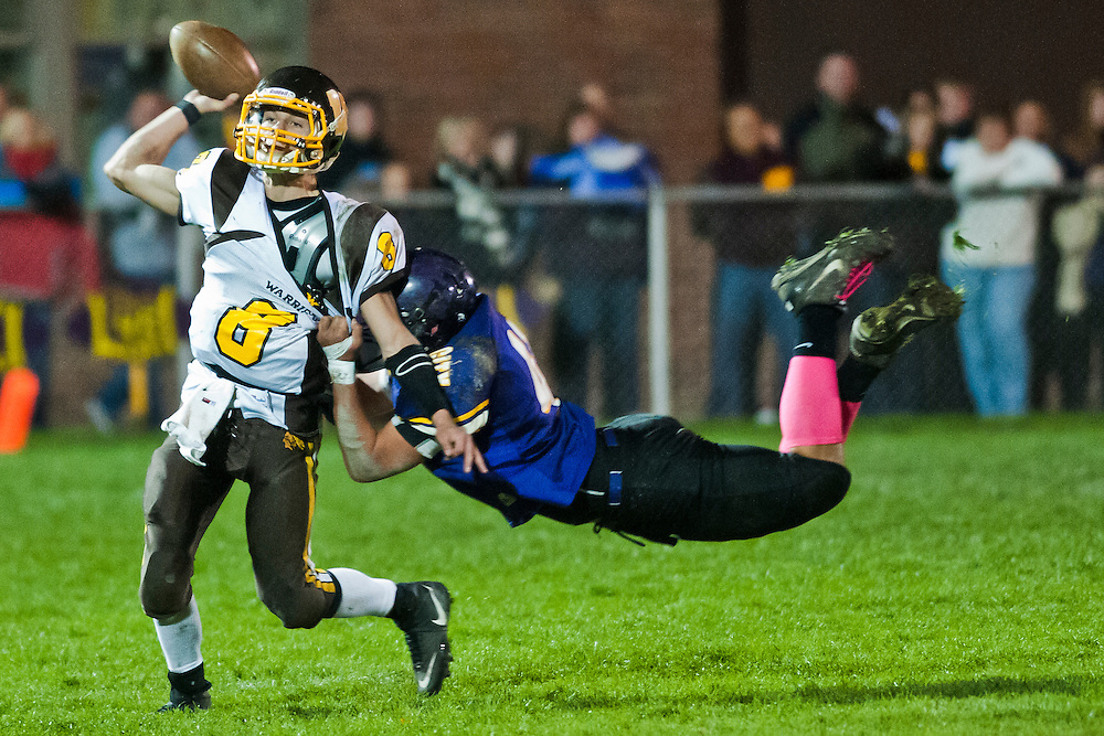 Bay City Western High School quarterback Austin Pichiotino throws the ball as Austin Rogers of Bay City Central High School attempts to tackle him during a football game at Bay City Central High School in Bay City, Mich., Friday, October 21, 2011.