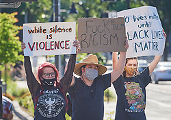 People hold signs at a June 3, 2020, Black Lives Matter protest in Eugene, Oregon. Participants were protesting the murder of George Floyd and other African-Americans by police.
