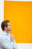 Close-up view of a thoughtful young man in front of wall painting
