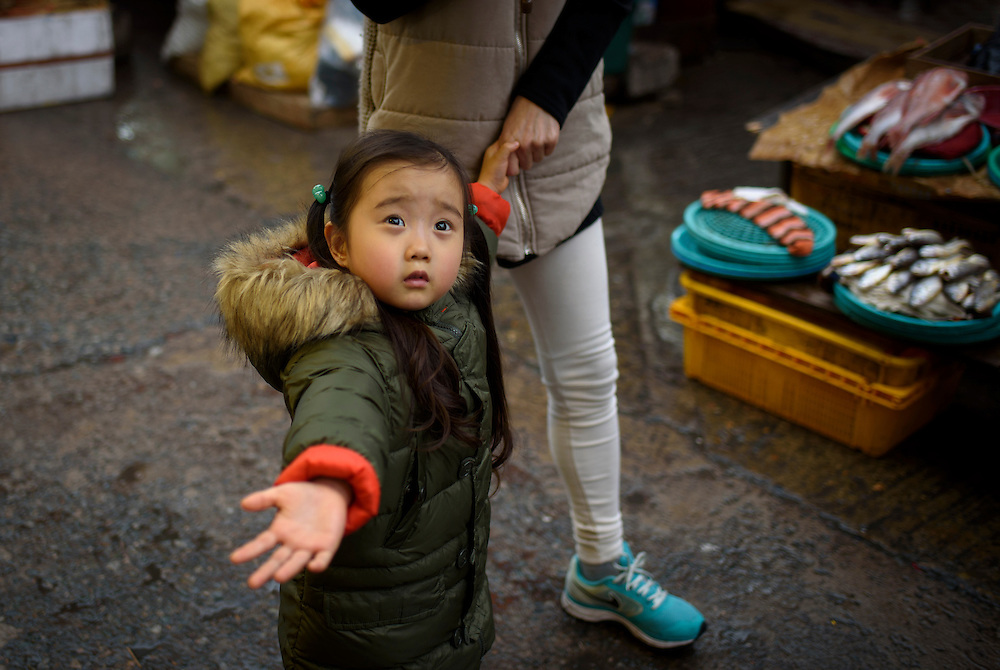 A girl walks with her mother in Jagalchi Market, Busan, South Korea.