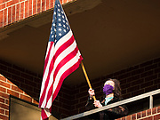 """08 APRIL 2020 - DES MOINES, IOWA: A woman wearing a face mask stands on her balcony and waves an American flag at Summit House, a condominium building for older adults. Residents are practicing """"social distancing"""" and always wear masks when they go outside of their units. On Wednesday evenings they stand on their porches for a few minutes to wave at passing cars and socialize. On Wednesday, 08 April, Iowa reported 1,145 confirmed cases of the Novel Coronavirus (SARS-CoV-2) and COVID-19. There have been 27 deaths attributed to COVID-19 in Iowa. Most non-essential businesses are closed until 30 April. There have been outbreaks of Coronavirus in several Iowa senior citizen housing complexes.        PHOTO BY JACK KURTZ"""