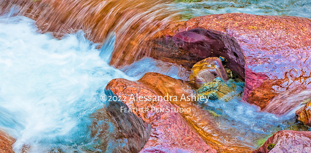 Rushing water highlights colored rocks at Avalanche Gorge, Glacier National Park, Montana, USA.