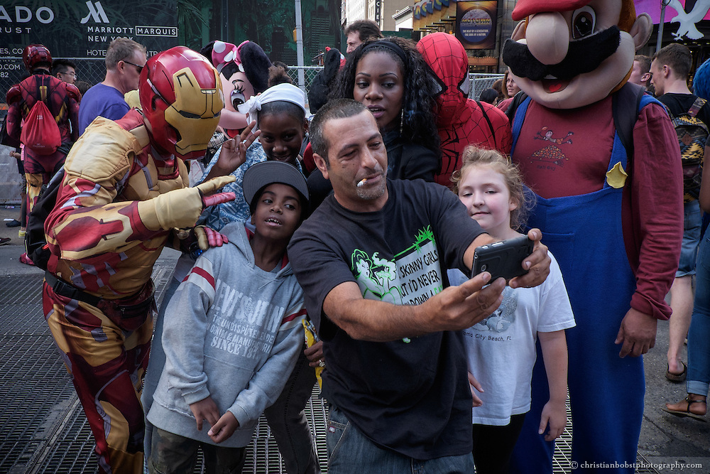 A tourist takes a selfie with some costumed characters and his family at Times Square in New York City.