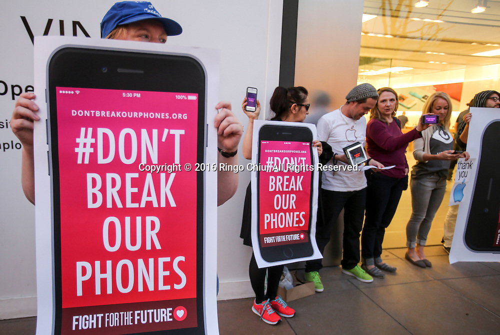 Demonstrators hold up signs  and iPhones during a rally in support of data privacy outside the Apple store, Tuesday, Feb. 23, 2016, in Los Angeles. Protesters assembled in more than 30 cities around the world to lash out at the FBI for obtaining a court order that requires Apple to make it easier to unlock an encrypted iPhone used by a gunman in December's mass murders in California.(Photo by Ringo Chiu/PHOTOFORMULA.com)<br /> <br /> Usage Notes: This content is intended for editorial use only. For other uses, additional clearances may be required.