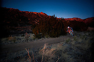 a man speeds through a corner while mountain biking fast at sunset.  horizontal wide angle composition taken in the sandia mountains of albuquerque, new mexico.