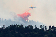 A air tanker dumps retardant on the Waldo Canyon fire west of Colorado Springs, Colorado June 24, 2012.  Firefighters in Western U.S. states struggled to contain out-of-control wind-stoked wildfires across the U.S. west as summer temperatures mounted, and a fresh blaze consumed more homes in Colorado.  REUTERS/Rick Wilking (UNITED STATES)