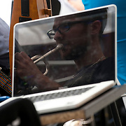 """June 21, 2014 - New York, NY : <br /> The city was flooded with music on Saturday as Make Music New York brought more than 1,300 free concerts to the city's streets and parks. The annual festival's program included the performance """"'In (Key)' - New Compositions in Celebration of Terry Riley's 'In C' @ 50 Years"""" on Cornelia Street, in front of the Cornelia Street Cafe in Greenwich Village, on Saturday afternoon. In addition to playing trumpet, musician and composer Adam Cuthbért performed software instruments using his computer.<br /> CREDIT: Karsten Moran for The New York Times"""