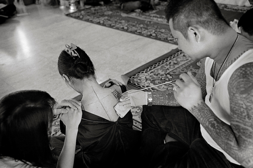 Thailand is a deeply spiritual country, in which both superstition and ritual tattooing play an active role. Traditional Thai tattoos are known as Yantra tattoos. They are believed to possess strong magical powers, which will protect the bearer as well as bring him or her good luck. With their alleged ability to break knife blades and stop bullets, this form of tattooing is particularly favoured by soldiers and the police force as well as, inevitably, by members of the underworld.<br /> <br /> Ajarn Noo Kanpai or Sompong Kanphai or ganpai. Famous around the world for the tattoos he did on Angelina Jolie. But in Thailand he is more famous for the magic he performs on the tattoos. He is the grand master of the art and has many followers and students. In the past, he trained has a Buddhist monk for many years and travelled to many temples to increase his knowlage of Sak Yant. Ajarn Noo Kamphai (Ajarn' meaning 'teacher of magical chanting or spell caster)<br /> <br /> Ajarn Noo does many blessing in a week. His life is very busy and demanding. His time is important to him for mediation and to continuing to increase his knowledge of the inner secrets of Sak Yant. There are several types of blessings he performs. A blessing with or without having a Sak Yant Tattoo. The next level is with a Sak Yant invisible oil tattoo which last about 5 minutes. This consist of oil being tattooed in to the skin and is made up of placements of dots in a pattern that represent the Sak Yant tattoo for which you want. Most ladies go for this as it does not show. He performs a magical spell / Yant / chant as he does the oil tattoo. When completed he performs a blessing for good luck and health.<br /> <br /> The next level is for him to tattoo a full ink Sak Yant tattoo with the magic and blessing. This takes longer and needs to be done by appointment only. If you want this service be prepared to thing about the cost as this is the biggest Sam Nak, which means office /tattoo studio in the worl