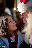JEROME A. POLLOS/Press..Mikkayla Wheaton, 6, talks to Santa during a visit during the Spirit Lake Christmas celebration Friday.