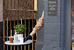 © Licensed to London News Pictures . 20/05/2020 . Manchester , UK . A coffee order is placed through a doorway on to a table with hand sanitiser , in the street outside Just Between Friends coffee shop , on Tib Street in Manchester's Northern Quarter . On the hottest day of the year so far independently run coffee shops and bars are open and trading with social distancing measures applied , after a period of being shut in an effort to reduce the spread of Covid-19 . Photo credit : Joel Goodman/LNP