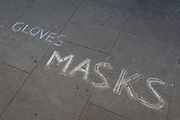 As the number of UK Coronavirus cases rose to over 8,000, it was announced that thousands of 15-minute home tests could be made available within days to those self-isolating with symptoms. Fading chalk writing is written on the pavement outside a now closed general store business selling gloves and masks in Camberwell, south London, on 25th March 2020, in London, England.
