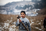 """Petr (11) posing with an axt on the way to the forest on a hill close to the Roma part of the district """"Podsadek"""" in eastern Slovakia. The city of Stara Lubovna is located about 100 km from Kosice in northeast Slovakia. The town has a population of 16350, of whom 2 060 (13%) are of Roma origin. The majority of Roma live in the Podsadek district, where 980 (74%) out of 1330 inhabitants are Roma."""