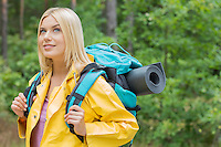 Smiling female backpacker in raincoat looking away at forest